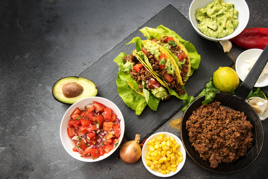 mexican tacos and ingredients like fried ground beef, tomato salsa, guacamole, corn and spices on a dark slate plate with copy space, top view from above, selected focus