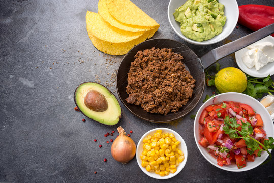 filling tacos with roasted beef, tomatoes, corn and guacamole, all ingredients on a dark stone background with copy space, top view from above