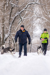 The father and son are walking with the husky dogs in the park in the winter.