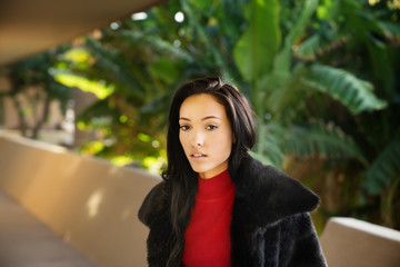Beautiful young woman wearing fake fur coat walking along apartment unit pathway