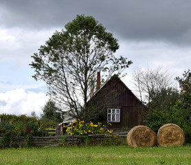 Old cottage, straw bale, yellow flowers, summer landscape on the Carpathian Mountains