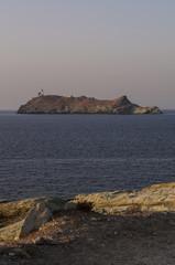 Corsica, 29/08/2017: tramonto sull'isola di Giraglia all'estremità settentrionale del Capo Corso nel Mar Mediterraneo, con vista del faro della Torre genovese