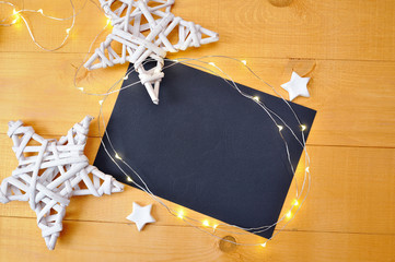 Christmas background black sheet of paper with place for your text and white christmas star and garland on a gold wooden background. Flat lay, top view photo mockup