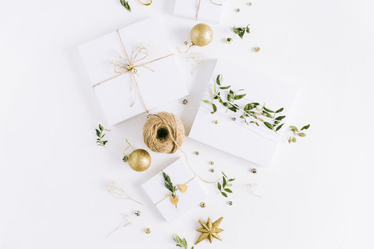 Handmade Christmas gift boxes and decoration accessories on white background. Flat lay, top view holiday composition.