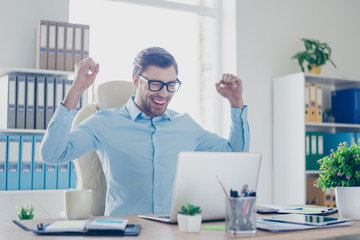 Excited young happy employer with raised hands in front of computer achieved success in his new start up or project for the first time
