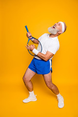 Full length of sexy emotional cool pensioner grandpa practising rock music on a  sport equipment, stands in pose, yell and shout. Body care, hobby, weight loss, lifestyle, strength and power, health