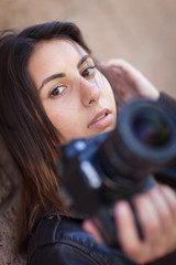 Young Adult Ethnic Female Photographer Against Wall Holding Camera.