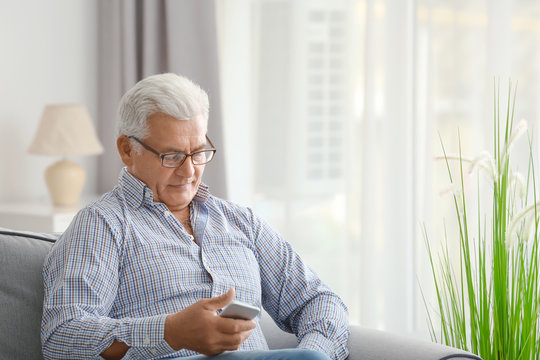 Handsome mature man with cell phone at home