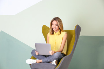 Young woman with laptop in armchair against color background