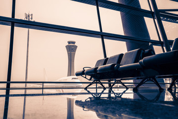 Empty chairs in the departure hall at the airport, with the control tower and the plane