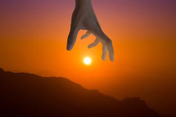 Hand catching the golden sun