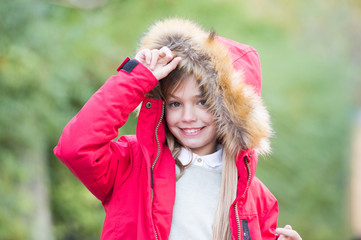 Child in red coat and hood with fur outdoor