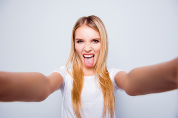 Funky crazy woman with blonde hair is showing her tongue and taking self portrait on her smartphone. She is isolated on grey background