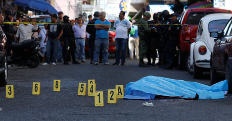 People and soldiers stand near at a crime scene where a man lies dead after being killed by unknown assailants outside a building in Chilpancingo,