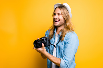 Smiling fashion photographer with modern digital camera in hands is shooting for his client. He loves his work