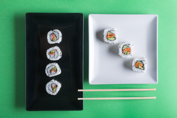 Japanese sushi on a green background. Rolls and chopsticks