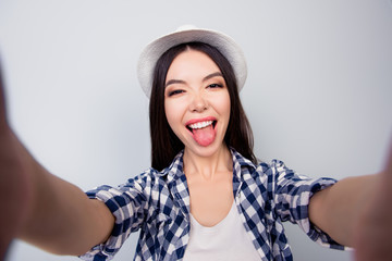 Pretty charming girl in casual clothes and hat is taking a self portarit and showing tongue. She is isolated on grey background
