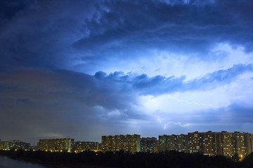 Cityscape at dusk with thunderstorm over apartments buildings
