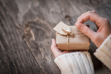 Female hands opening gift box over wooden background and space for text