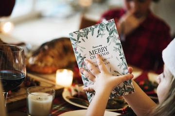 Kid holding Christmas menu card