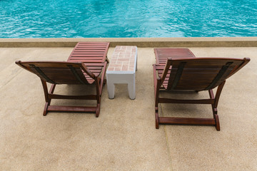 Wooden sun loungers on yellow polished stone floor at the edge of the pool