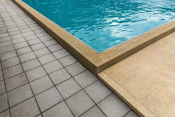 Swimming pool with cement blocks pathway and yellow polished stone floor