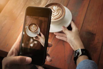Young girl using Photography of smartphone of latte art coffee o