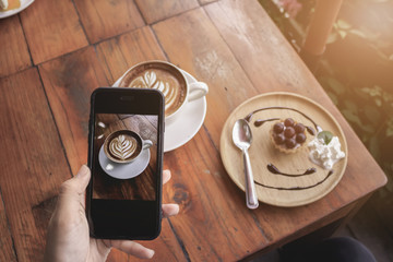 young girl hand holding smartphone for Photo of latte art coffee