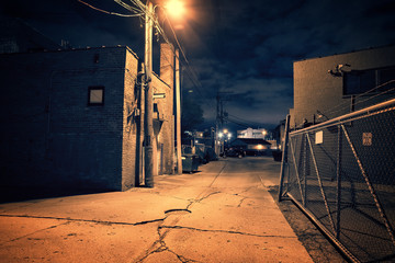 Scary dark city Chicago alley next to an urban warehouse and parking lot. Wall mural