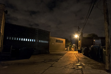 Fotomurales - Scary dark city Chicago alley next to an urban warehouse.