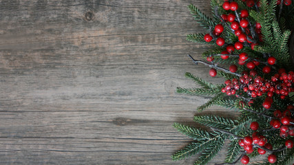Christmas Evergreen Branches and Berries Over Rustic Wood Horizontal Background
