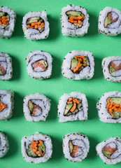 Japanese sushi on a green background. Rolls for dinner or lunch
