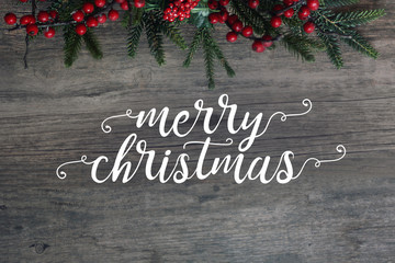 Merry Christmas Calligraphy with Evergreen Branches and Berries Over Dark Rustic Wood Background