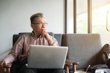 asian senior man using laptop