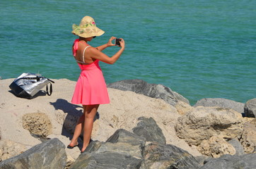 A woman wearing a pink sundress and a straw at taking an iPhone photograph of the beach at south pointe park in Miami Beach,Florida