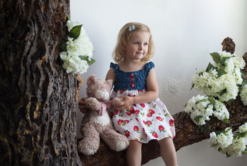 Portrait of a little girl sitting on a tree. Portrait, childhood, family values.