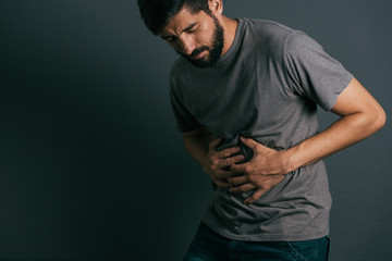 Young man suffering from stomach ache standing