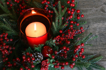 Holiday Christmas Candle with Pine Tree Branches and Berries Over Rustic Wood Background