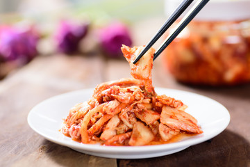 Korean food, kimchi cabbage on white dish with chopsticks for eating.Healthy food