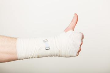Man with bandaged hand showing thumb up.