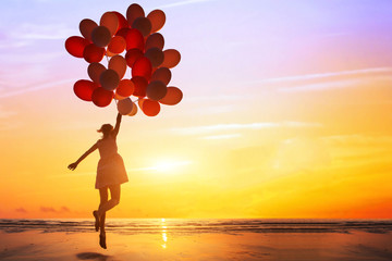 happiness or dream concept, silhouette of happy woman jumping with multicolored balloons at sunset on the beach