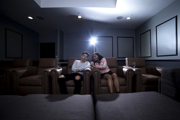 Interracial couple on a movie date in a living room with a home theater system with seats.  They are drinking red wine on glass.  They are watching a movie or television.