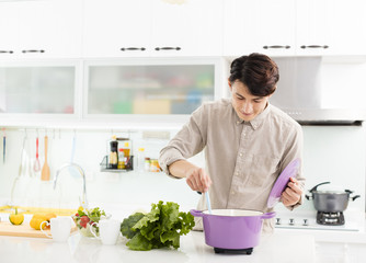 young man cooking at home in kitchen.