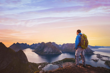 travel and adventure background, hiker with backpack enjoying sunset landscape in Lofoten, Norway
