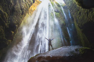 travel to Iceland, person with raised hands standing in waterfall Gljufrabui, inspired happy traveler enjoying nature, adventure concept.