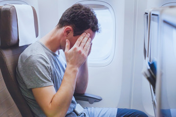 headache in the airplane, man passenger afraid and feeling bad during the flight in plane Wall mural