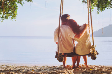 romantic holidays for two, affectionate couple sitting together on the beach on swing, silhouette of man hugging woman