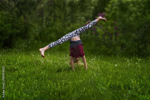 Teenage slim girl does handstand on the grass in summer day  Legs