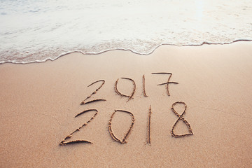 new year change 2017 to 2018, calendar dates written on the sand of beach