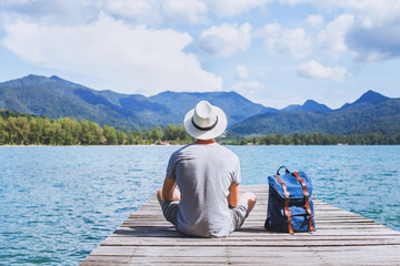summer travel, young romantic man tourist wanderlust sitting on wooden pier